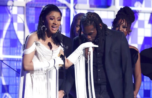 "(Photo by Matt Sayles/Invision/AP). Cardi B, left, accepts the award for best rap album for ""Invasion of Privacy"" as Offset kisses her hand at the 61st annual Grammy Awards on Sunday, Feb. 10, 2019, in Los Angeles."