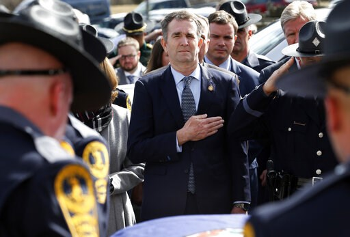 (AP Photo/Steve Helber, Pool). Virginia Gov. Ralph Northam, left, and his wife Pam, watch as the casket of fallen Virginia State Trooper Lucas B. Dowell is carried to a waiting tactical vehicle during the funeral at the Chilhowie Christian Church in Ch...