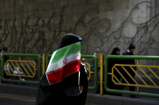 (AP Photo/Ebrahim Noroozi, File). FILE - In this Feb. 11, 2016 file photograph, an Iranian woman holds the national flag during a rally commemorating the 37th anniversary of the Islamic revolution, in Tehran, Iran. Iran's 1979 Islamic Revolution initia...