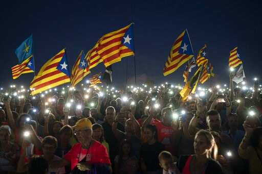 """(AP Photo/Felipe Dana, File). FILE - In this Sunday, Sept. 30, 2018 file photo, pro-independence demonstrators wave """"esteladas"""" or independence flags, as they sing in a field overlooking the Lledoners prison in Sant Joan de Vilatorrada, about 50 kilome..."""