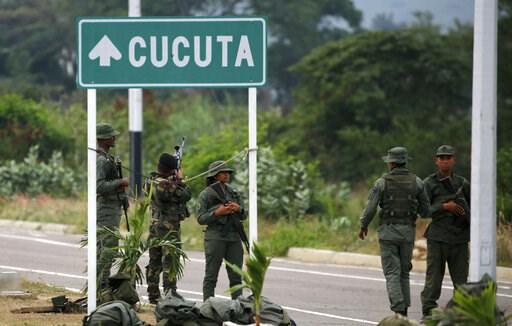 (AP Photo/Fernando Llano). Venezuelan Bolivarian Army soldiers stand guard at the Tienditas International Bridge that links Colombia and Venezuela, near Urena, Venezuela, Friday, Feb. 8, 2019. As humanitarian aid kits were being packed into individual ...