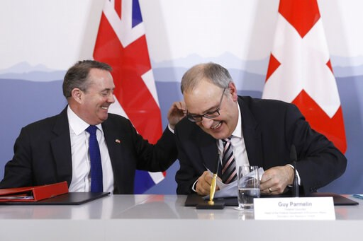 (Peter Klaunzer/Keystone via AP). Swiss Federal Councillor Guy Parmelin, right, and British Secretary of State for International Trade Liam Fox, left, react after signing a trade agreement in Bern, Switzerland, Monday, Feb. 11, 2019. Parmelin and Fox s...
