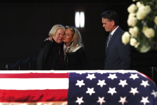 (AP Photo/Paul Sancya). Rep. Debbie Dingell, D-Mich., center, consoles former Rep. Candice Miller, R-Mich., as Macomb County executive Mark Hackel, right, looks on at the casket of her husband and former Rep. John Dingell, lying in repose in Dearborn, ...