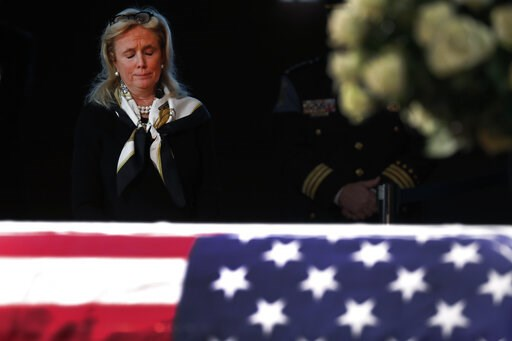 (AP Photo/Paul Sancya). Rep. Debbie Dingell, D-Mich., stands near the casket of her husband and former Rep. John Dingell lying in repose in Dearborn, Mich., Monday, Feb. 11, 2019. John Dingell, the longest-serving member of Congress in American history...