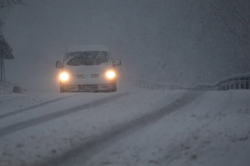 (AP Photo/Amel Emric). A car drives through a snow storm on a road near Sarajevo, Bosnia, Monday, Feb. 11, 2019. Heavy snow descended on the Balkan countries causing havoc throughout the region.