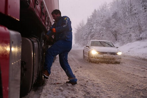 (AP Photo/Amel Emric). Bosnian truck driver checks tyres on the truck during a snow storm on a road near Sarajevo, Bosnia, Monday, Feb. 11, 2019. Heavy snow has descended on the Balkan countries of eastern Europe, causing havoc throughout the region.
