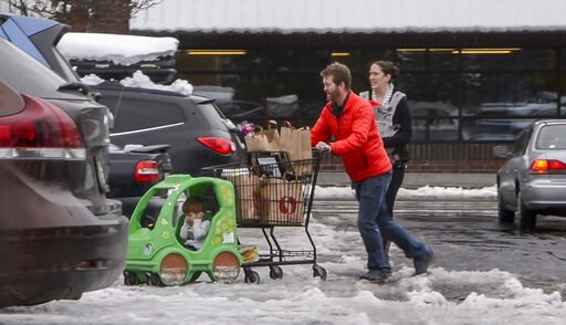 (Peter Haley/The News Tribune via AP). Jesse and Sarah Fees have their children along on a trip in North Tacoma, Wash., to restock their kitchen, Sunday, Feb. 10, 2019. Pacific Northwest residents who are more accustomed to rain than snow were digging ...