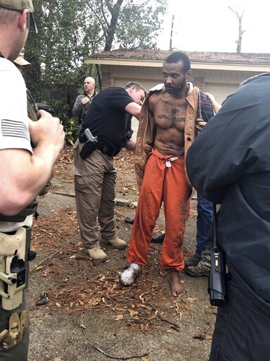 (Conroe Police Department via AP). FILE - This Feb. 3, 2019 photo released by the Conroe Police Department shows Cedric Marks being captured after nine-hour manhunt that began when he escaped from a prisoner transport van in Conroe, Texas. A private pr...