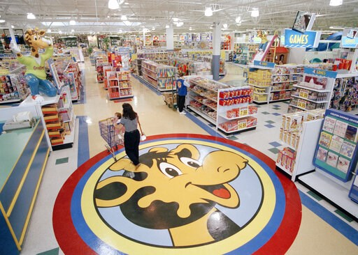 (AP Photo/Daniel Hulshizer, File). FILE- In this July 30, 1996, file photo, a woman pushes a shopping cart over a graphic of Toys R Us mascot Geoffrey the giraffe at the Toys R Us store in Raritan, N.J. Richard Barry, a former Toys R Us executive and n...