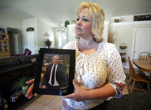 (AP Photo/Rick Bowmer, File). FILE - In this July 13, 2016 file photo, Laurie Holt holds a photograph of her son Joshua Holt at her home in Riverton, Utah. Holt, a Utah woman who spent nearly two years pushing to get her son freed from a Venezuelan jai...