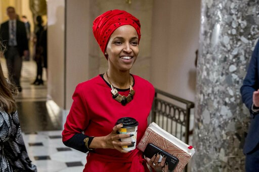 (AP Photo/Andrew Harnik). In this Jan. 16, 2019 file photo, Rep. Ilhan Omar, D-Minn., center, walks through the halls of the Capitol Building in Washington.