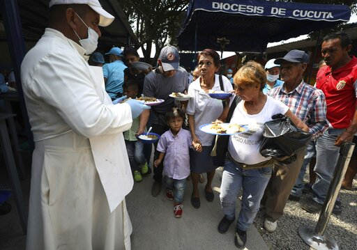 "(AP Photo/Fernando Vergara). Priest Richard Garcia  hands out free lunches to Venezuelan migrants at the ""Divina Providencia"" migrant shelter in La Parada, near Cucuta, on the border with Venezuela, Colombia, Monday, Feb. 11, 2019. Millions of Venezuel..."