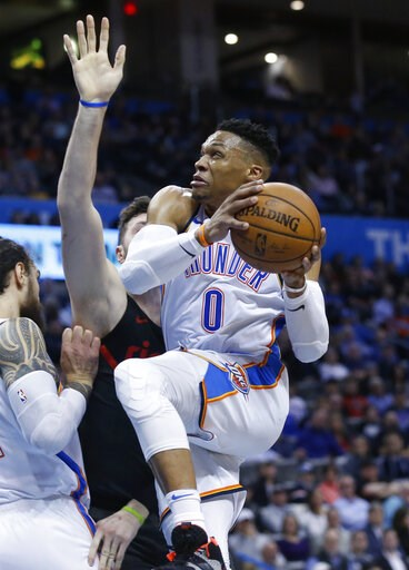 (AP Photo/Sue Ogrocki). Oklahoma City Thunder guard Russell Westbrook, right, goes to the basket past Portland Trail Blazers center Jusuf Nurkic, center, in the first half of an NBA basketball game in Oklahoma City, Monday, Feb. 11, 2019.