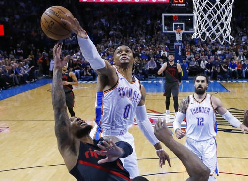 (AP Photo/Sue Ogrocki). Oklahoma City Thunder guard Russell Westbrook (0) blocks a shot by Portland Trail Blazers guard Damian Lillard, left, in the first half of an NBA basketball game in Oklahoma City, Monday, Feb. 11, 2019.