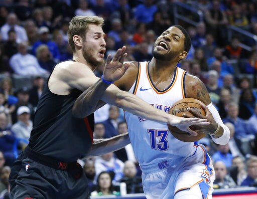 (AP Photo/Sue Ogrocki). Oklahoma City Thunder forward Paul George (13) is fouled by Portland Trail Blazers forward Jake Layman, left, as he drives to the basket in the first half of an NBA basketball game in Oklahoma City, Monday, Feb. 11, 2019.