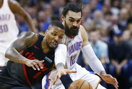 (AP Photo/Sue Ogrocki). Portland Trail Blazers guard Damian Lillard (0) and Oklahoma City Thunder center Steven Adams (12) reach for the ball in the first half of an NBA basketball game in Oklahoma City, Monday, Feb. 11, 2019.