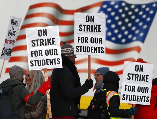 (AP Photo/David Zalubowski). Teachers carry placards as they walk a picket line outside South High School early Monday, Feb. 11, 2019, in Denver. The strike on Monday is the first for teachers in Colorado in 25 years after failed negotiations with the ...