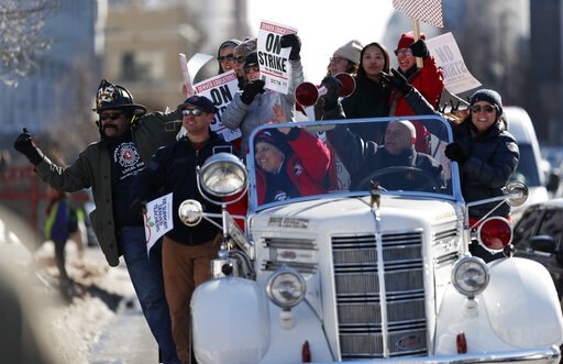 (AP Photo/David Zalubowski). Denver teachers ride on the back of a vintage Denver Fire Department truck past a strike rally on the west steps of the State Capitol Monday, Feb. 11, 2019, in Denver. The strike is the first for teachers in Denver since 19...