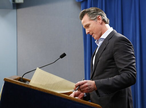 (AP Photo/Rich Pedroncelli). California Gov. Gavin Newsom prepares to sign an executive order to withdraw most of the National Guard troops from the nation's southern border and changing their mission, during a Capitol news conference Monday, Feb. 11, ...