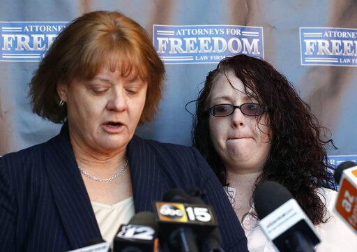 (AP Photo/Matt York). Anya Chapman, right, listens as attorney Jody Broaddus reads Chapman's statement to the media concerning Chapman's husband, Johnny Wheatcroft, Monday, Feb. 11, 2019, in Chandler, Ariz. Broaddus has filed a lawsuit on behalf of Whe...