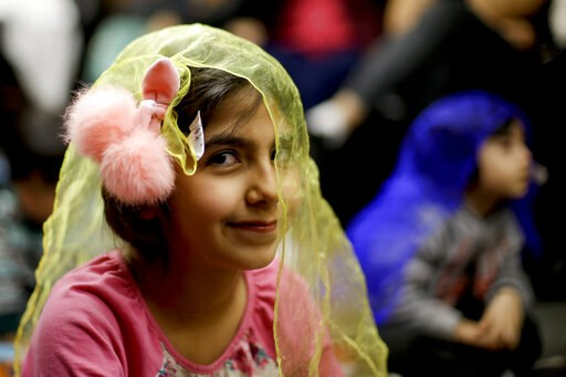 (AP Photo/Chris Carlson). In this Wednesday, Jan. 23, 2019, photo, Melorin Issarezal 8, plays with a scarf during Persian story time at Irvine public library in Irvine, Calif. It's been four decades since the Iranian revolution overthrew the ruling sha...