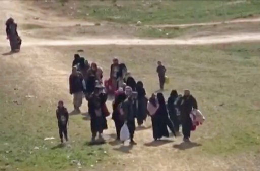 (ANHA via AP). In this Sunday, Feb. 10, 2019 image from video provided by Hawar News Agency, ANHA, an online Kurdish news service, civilians flee fighting near Baghouz, Syria. Fierce fighting was underway Monday between U.S.-backed Syrian forces and th...