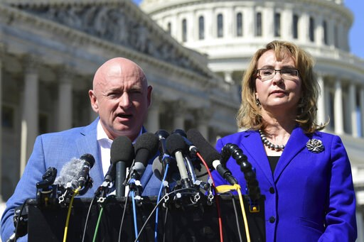 (AP Photo/Susan Walsh, File). FILE- In this Oct. 2, 2017, file photo former Rep. Gabrielle Giffords, D-Ariz., right, listens as her husband Mark Kelly, left, speaks on Capitol Hill in Washington. Kelly said Tuesday, Feb. 12, 2019, that he's running to ...