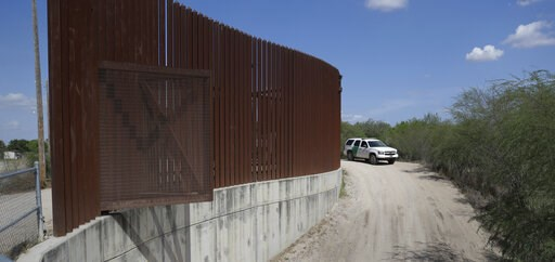 (AP Photo/Eric Gay, File). FILE - In this Aug. 11, 2017, file photo, a U.S. Customs and Border Patrol vehicle passes along a section of border levee wall in Hidalgo, Texas. The U.S. government is preparing to begin construction of more border walls and...