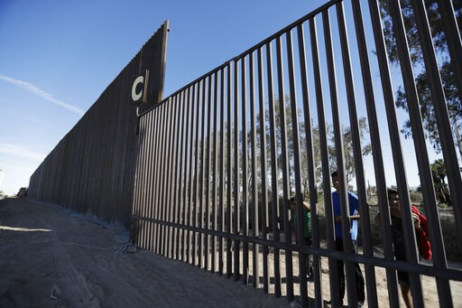 (AP Photo/Gregory Bull, File). FILE - In this March 5, 2018, file photo, boys look through an older section of the border structure from Mexicali, Mexico, alongside a newly-constructed, taller section, left, in Calexico, Calif. A federal appeals court ...