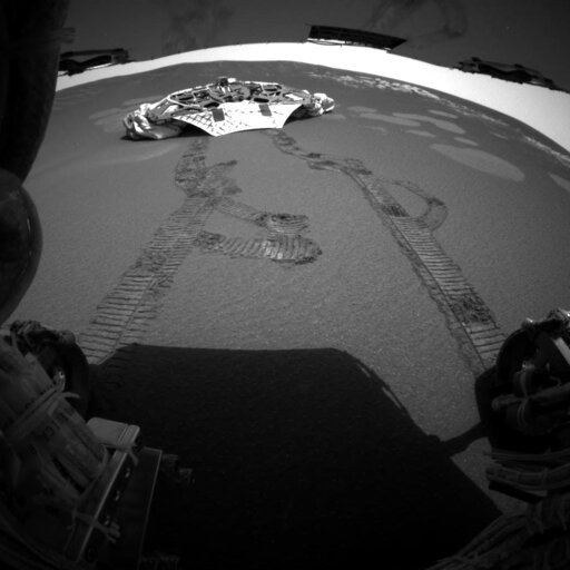 (NASA/JPL via AP). FILE - This photo released Thursday, Feb. 5, 2004 made by one of the rear hazard-avoidance cameras on NASA's Opportunity rover, shows Opportunity's landing platform, with freshly made tracks leading away from it. Opportunity rolled a...