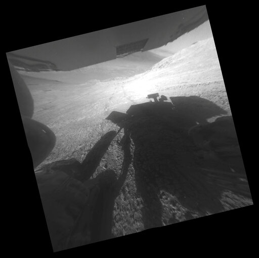 (NASA/JPL-Caltech via AP). This March 22, 2016 photo made available by NASA shows the shadow and wheel tracks of the Mars Exploration Rover Opportunity just after a drive on a slope above Endeavour Crater. The image has been rotated 13.5 degrees to adj...