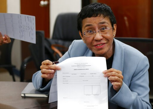 (AP Photo/Bullit Marquez). Maria Ressa, the award-winning head of a Philippine online news site Rappler that has aggressively covered President Rodrigo Duterte's policies, shows an arrest form after being arrested by National Bureau of Investigation ag...