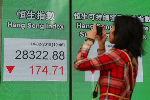 (AP Photo/Kin Cheung). A woman takes a photograph in front of an electronic board showing Hong Kong share index outside a bank in Hong Kong, Thursday, Feb. 14, 2019.