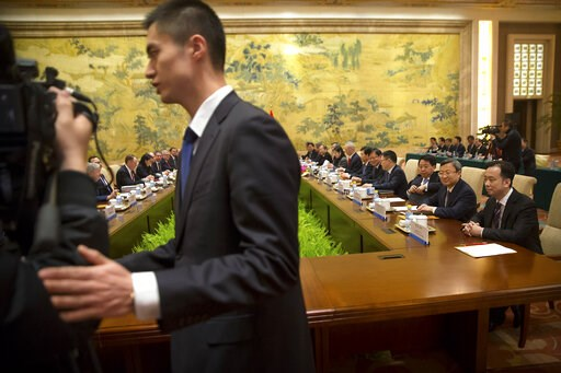(AP Photo/Mark Schiefelbein, Pool). A security official escorts journalists from the opening session of trade negotiations between U.S. and Chinese trade representatives at the Diaoyutai State Guesthouse in Beijing, Thursday, Feb. 14, 2019.