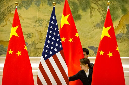 (AP Photo/Mark Schiefelbein, Pool). Chinese staffers adjust U.S. and Chinese flags before the opening session of trade negotiations between U.S. and Chinese trade representatives at the Diaoyutai State Guesthouse in Beijing, Thursday, Feb. 14, 2019.
