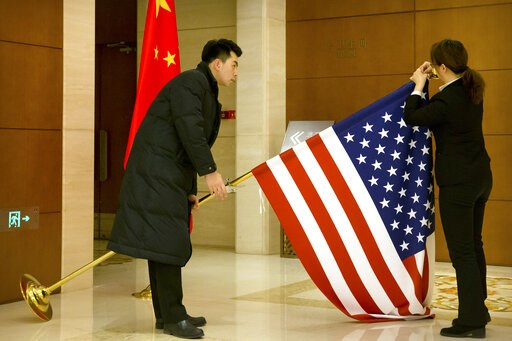 (AP Photo/Mark Schiefelbein, Pool). Chinese staffers adjust a U.S. flag before the opening session of trade negotiations between U.S. and Chinese trade representatives at the Diaoyutai State Guesthouse in Beijing, Thursday, Feb. 14, 2019.
