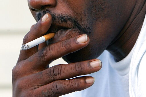 (AP Photo/Ric Feld). FILE - In this Oct. 4, 2005 file photo, a man smokes a cigarette in Euharlee, Ga. According to a report by the American Cancer Society released on Thursday, Feb. 14, 2019, cancer deaths have dropped for all Americans, but the rates...