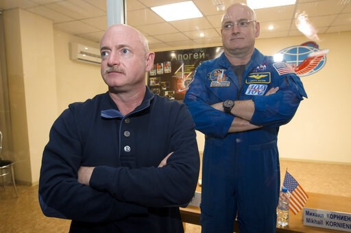(AP Photo/Dmitry Lovetsky). FILE - In this March 26, 2015 file photo, U.S. astronaut Scott Kelly, right, crew member of the mission to the International Space Station, stands behind glass in a quarantine room, behind his brother, Mark Kelly, also an as...