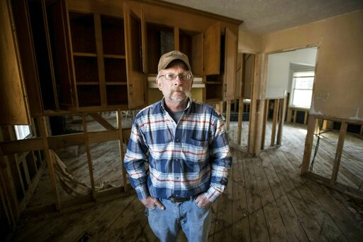 (AP Photo/Sean Rayford). Kevin Tovornik poses for a photo in the kitchen of his home damaged by flooding from Hurricane Florence near the Crabtree Swamp Friday, Feb. 1, 2019, in Conway, S.C. Tovornik is currently living in his back yard in a camper tra...