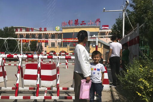 (AP Photo/Ng Han Guan, File). FILE - In this Aug. 31, 2018, file photo, a child and a woman wait outside a school entrance mounted with surveillance cameras and barricades with multiple layers of barbed wire in Peyzawat, western China's Xinjiang region...