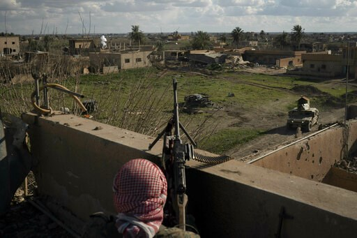 (AP Photo/Felipe Dana). A U.S.-backed Syrian Democratic Forces (SDF) fighter stands atop a building used as a temporary base near the last land still held by Islamic State militants in Baghouz, Syria, Monday, Feb. 18, 2019. Hundreds of Islamic State mi...