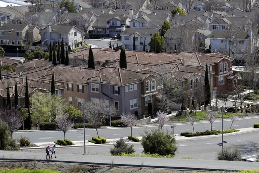 (AP Photo/Marcio Jose Sanchez, File). FILE - In this March 6, 2018, file photo, people walk along a path in front of a row of homes in San Jose, Calif. The suburbs are usually seen as the great political swing area in the United States, toggling back a...