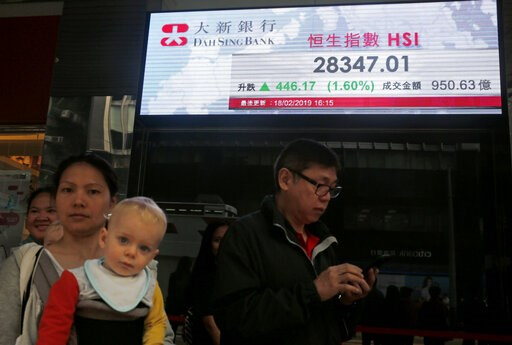 (AP Photo/Kin Cheung). People walk past an electronic board showing Hong Kong share index outside a bank in Hong Kong, Wednesday, Feb. 20, 2019. Shares were mostly higher in Asia on Wednesday after a modestly high finish on Wall Street that extended th...