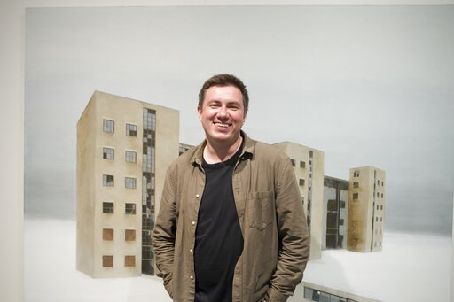 "(Pavel Otdelnov, Photo via AP). In this handout photo taken in 2018, Pavel Otdelnov, a Russian artist poses for a photo in front of his work ""Ruins. Building 538» in Moscow, Russia . Pavel Otdelnov, a Russian artist who grew up in Dzerzhinsk, the cente..."