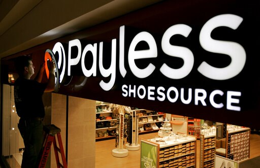 (AP Photo/Charlie Riedel, File). FILE- In this May 18, 2006, file photo a worker puts the finishing touches on a sign unveiling the company's new look at a Payless Shoesource store at a mall in Independence, Mo. Payless ShoeSource has filed for Chapter...