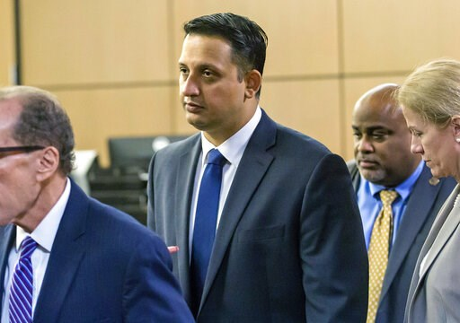 (Lanes Waters/Palm Beach Post via AP). In this Jan. 18, 2019 photo, Nouman Raja leaves the courtroom with his legal team after a pre-trial hearing in West Palm Beach, Fla. The fired Palm Beach Gardens police officer's trial begins with jury selection T...