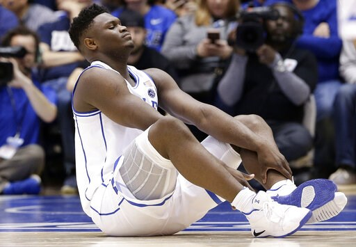 (AP Photo/Gerry Broome). Duke's Zion Williamson sits on the floor following a injury during the first half of an NCAA college basketball game against North Carolina in Durham, N.C., Wednesday, Feb. 20, 2019.
