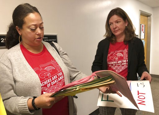 (AP Photo/Kathleen Ronayne). Eyana Spencer, principal at Manzanita Community School, left, and Katherine Carter, a principal at Oakland School of Language, look over their schedule for meeting with California lawmakers about Oakland school funding duri...