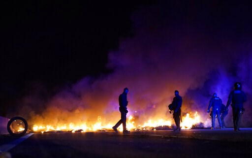 (AP Photo/Daniel Cole). Police officers try to remove burning tires, set by demonstrators to block a highway in protest of the imprisonment of pro-independence political leaders during a general strike in Catalonia, Spain, Thursday, Feb. 21, 2019.