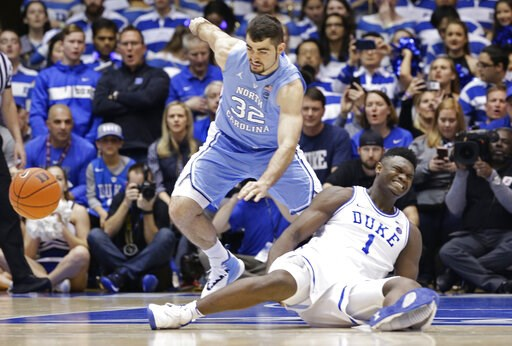 (AP Photo/Gerry Broome). Duke's Zion Williamson (1) falls to the floor with an injury while chasing the ball with North Carolina's Luke Maye (32) during the first half of an NCAA college basketball game in Durham, N.C., Wednesday, Feb. 20, 2019.